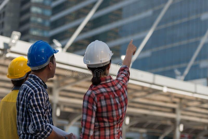 Den asiatiska teknikergruppen konsulterar konstruktion på platsbyggnadsarbete royaltyfria bilder