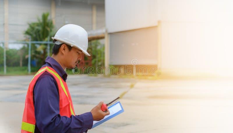 Den asiatiska teknikern i säkerhetslikformig och hållande walkie-talkie för vithjälm och skrivplattan på suddig bransch planterar royaltyfria bilder