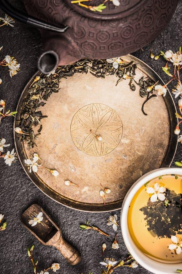 Den asiatiska teservisen med järntekannan och sakura blomstrar på lantlig bakgrund för tappning, bästa sikt royaltyfria foton