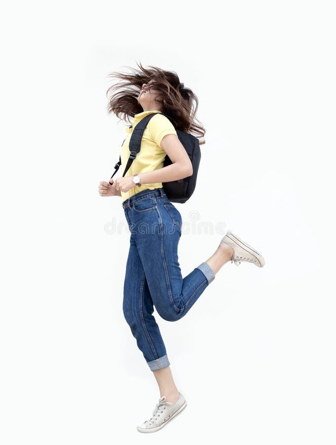 Den asiatiska tonårs- flickan hoppar knackar med ryggsäcken arkivbild