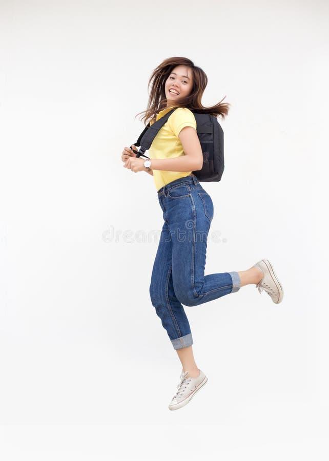 Den asiatiska tonårs- flickan hoppar knackar med ryggsäcken arkivfoto