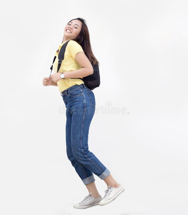 Den asiatiska tonårs- flickan hoppar knackar med ryggsäcken arkivbilder