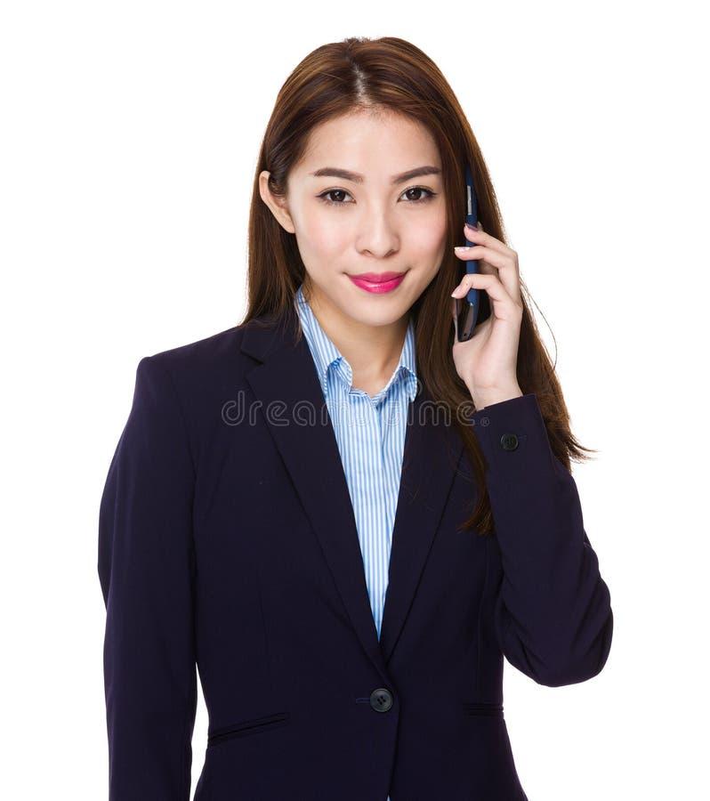 Den asiatiska unga affärskvinnan gör en appell royaltyfri fotografi