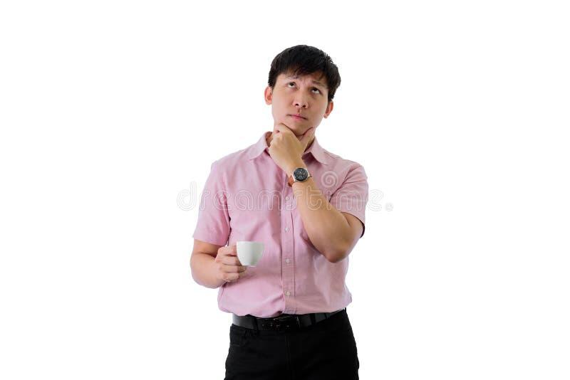 Den asiatiska unga aff?rsmannen har anseende och planl?ggningen f?r aff?rsm?l med en kopp kaffe p? isolerat p? wihtebakgrund fotografering för bildbyråer