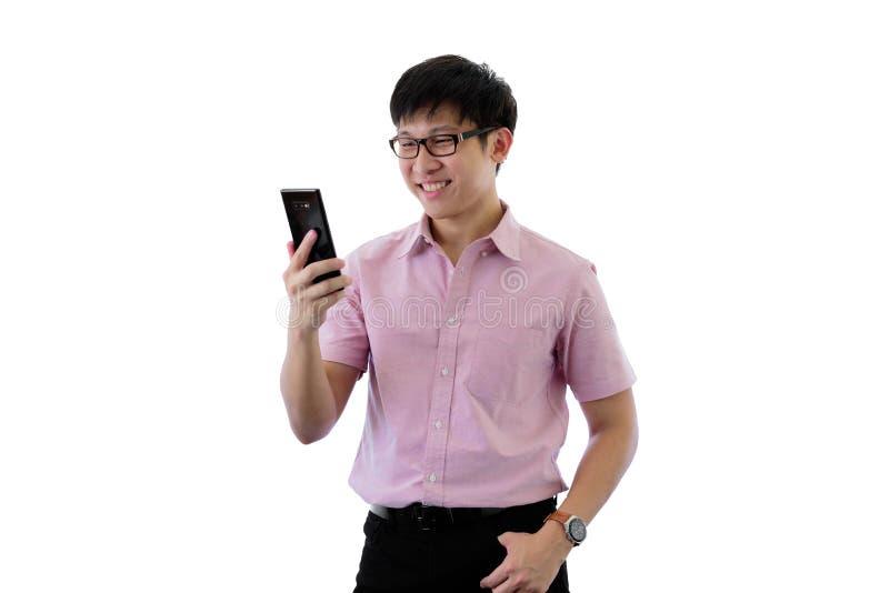 Den asiatiska unga aff?rsmannen har st?ende och att spela telefonen med lyckligt p? isolerat p? wihtebakgrund fotografering för bildbyråer