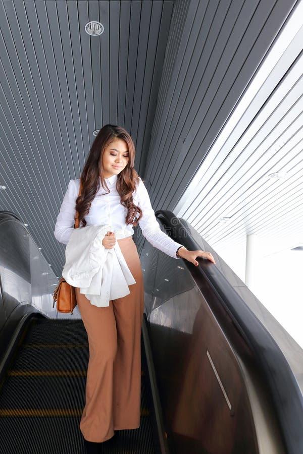 Den asiatiska unga kvinnan går klättringrulltrappan fotografering för bildbyråer