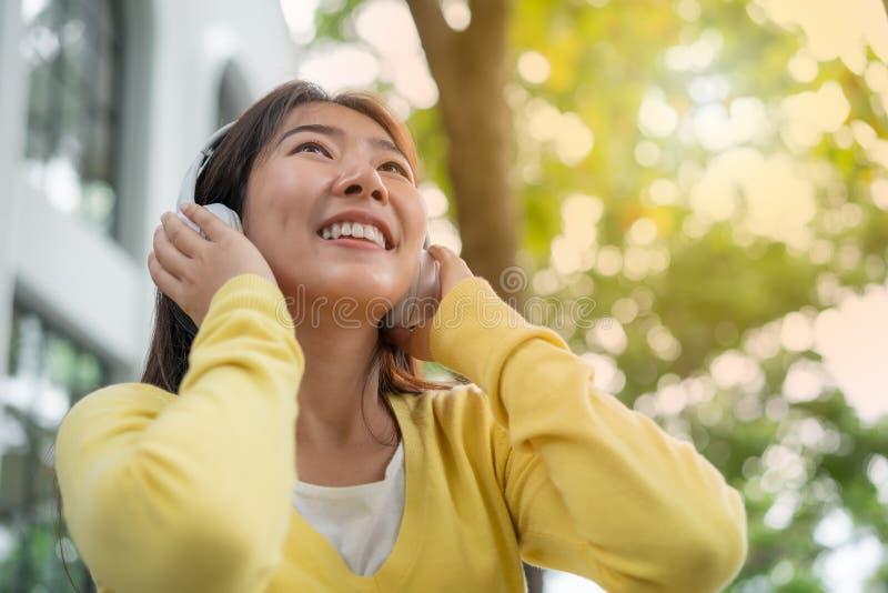 Den asiatiska unga kvinnan med lyssnande musik f?r h?rlurar i det fria arbeta i tr?dg?rden arkivbild