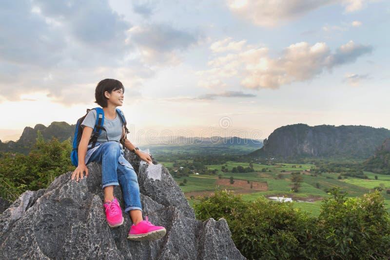 den asiatiska unga kvinnan med ryggsäcksammanträde vaggar på av berget, tra royaltyfria foton