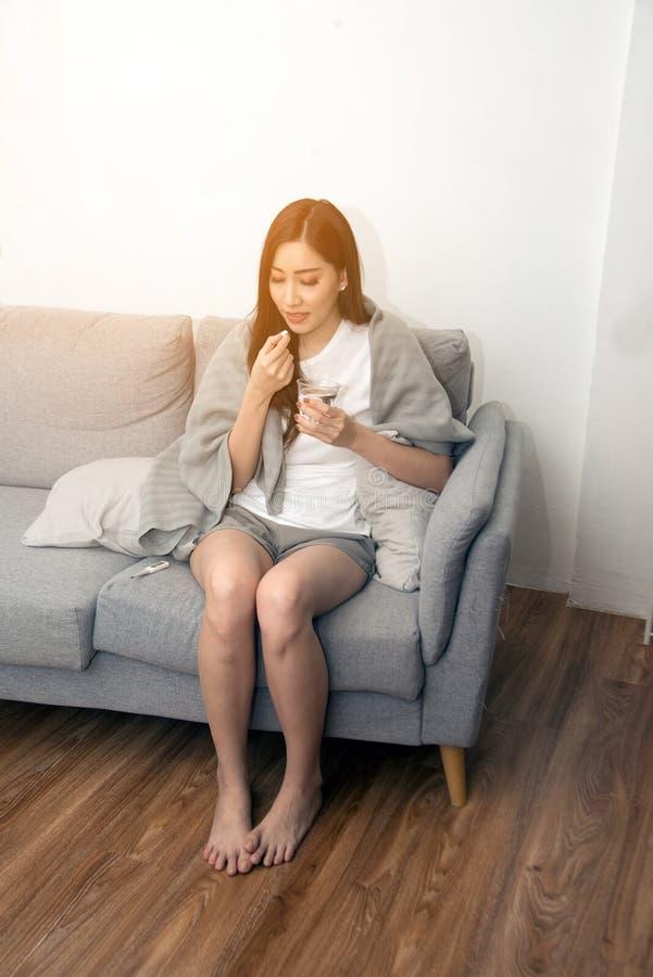 Den asiatiska unga kvinnan slogg in i en filt och under sjukdom och taantipyretics fotografering för bildbyråer