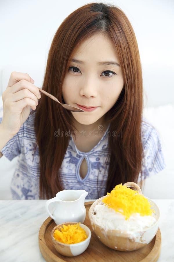 Den asiatiska unga kvinnan som äter rakad is med, mjölkar och kokosnöten arkivbilder