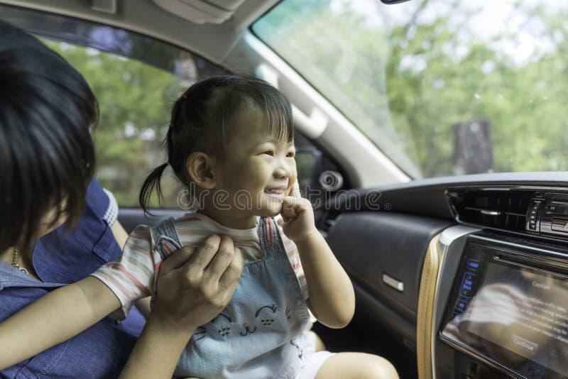 Den asiatiska ungeflickan är lycka i bilen royaltyfria foton