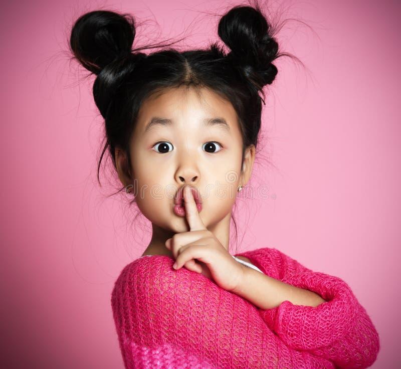 Den asiatiska ungeflickan i rosa tröja visar shh teckenslut upp ståenden arkivbild