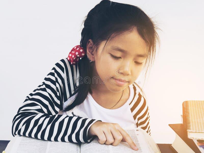 Den asiatiska ungen är läseboken royaltyfria foton