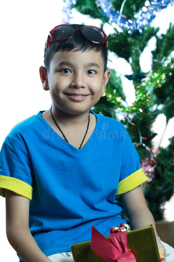 Den asiatiska ungen med roligt leende efter får hans julgåva arkivbild