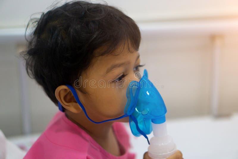 Den asiatiska ungepojken 3 gamla år har sjukt i nebulizermaskering royaltyfria foton