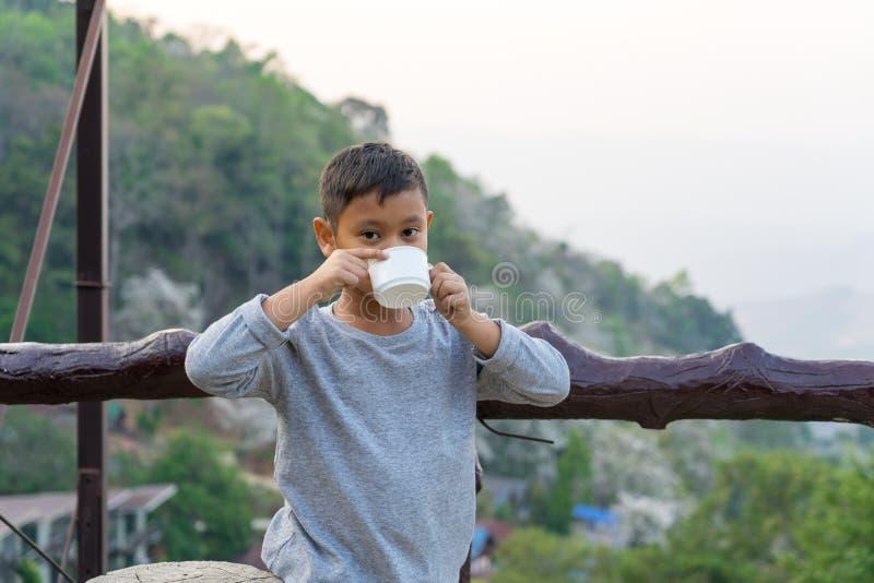 Den asiatiska ungepojken ?r dricksvatten fr?n exponeringsglaset Med bakgrund f?r bergsikter arkivfoto