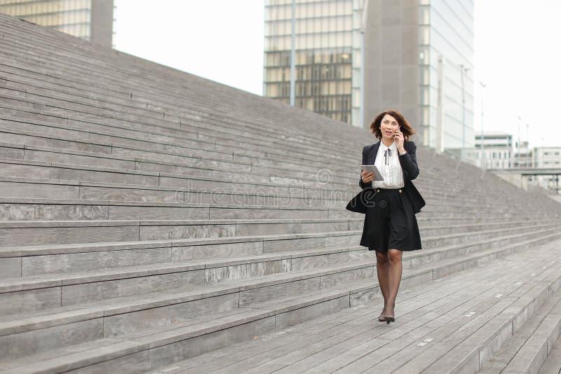 den asiatiska utseendemässiga affärskvinnan promenerar att tala för trappa arkivfoto