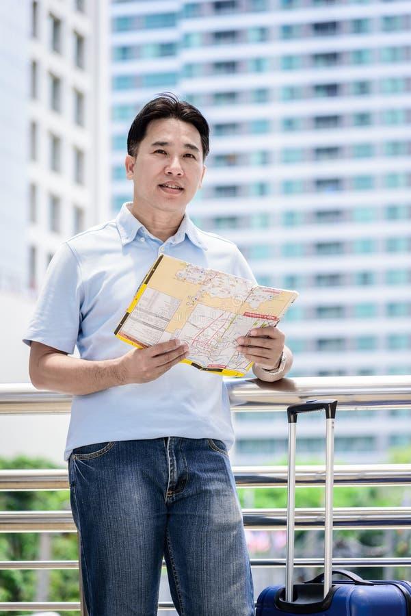 Den asiatiska vuxna turisten har att se och att planera för att resa royaltyfri bild