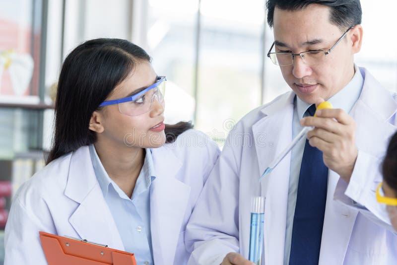 Den asiatiska youndstudentforskaren som forskar och l?r med den h?ga forskaren, har undervisande bakgrund i ett laboratorium royaltyfria bilder