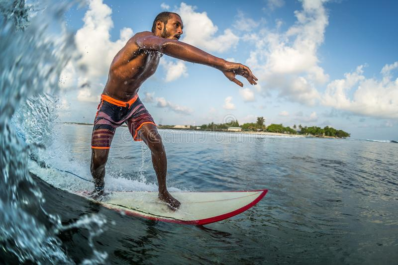 Den asiatiska yrkesmässiga surfaren rider havvågen royaltyfri bild