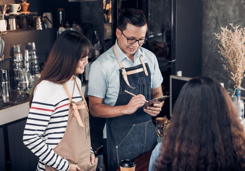 Den Asien Barista uppassaren tar beställning från kund i coffee shop, två royaltyfri foto