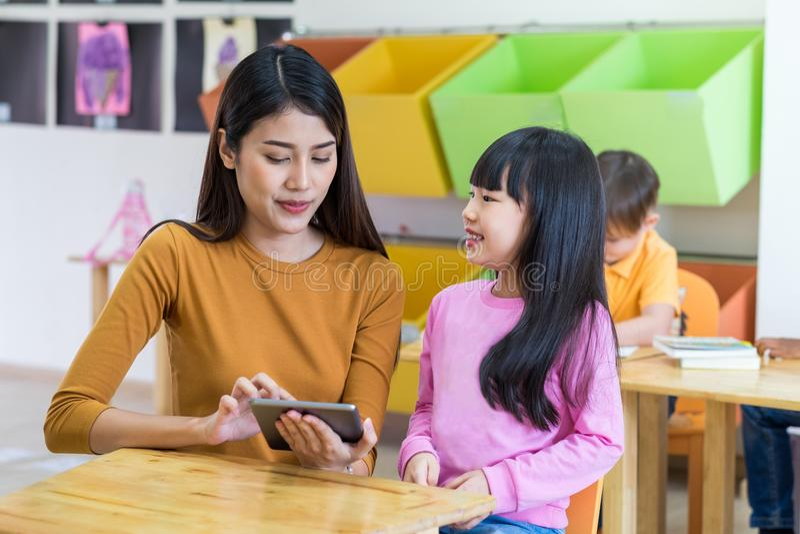Den Asien kvinnaläraren undervisar flickastudenten med minnestavladatoren i cl arkivbild