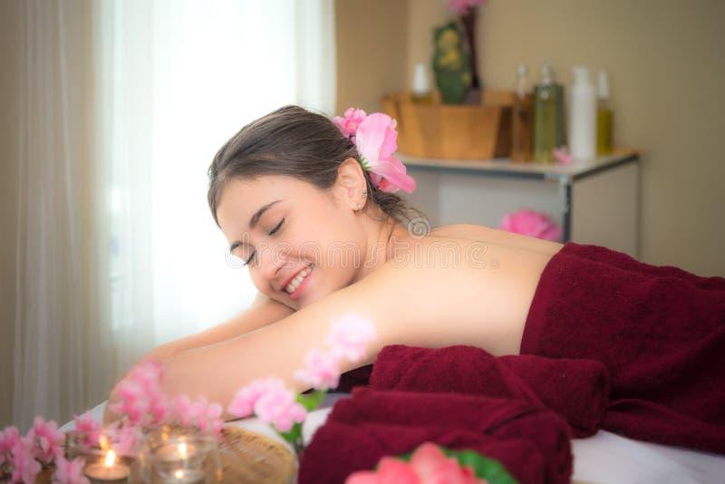 Den Asien skönhetkvinnan som ner ligger på massagesäng med, skurar socker och salt arom på den thailändska brunnsort- och wellnes royaltyfri bild