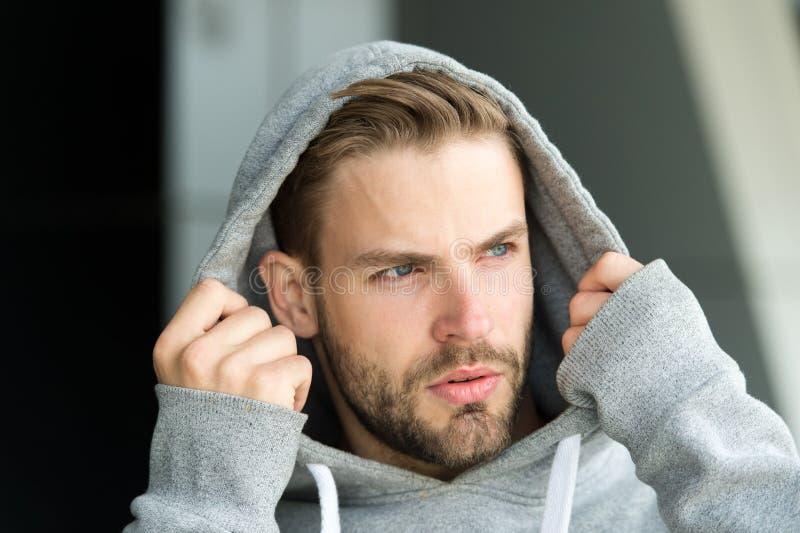 Den attraktiv grabben som uppsökas och, sätter på huven Manlighetbegrepp Man med borstet på den allvarliga framsidan, stads- bakg royaltyfri foto