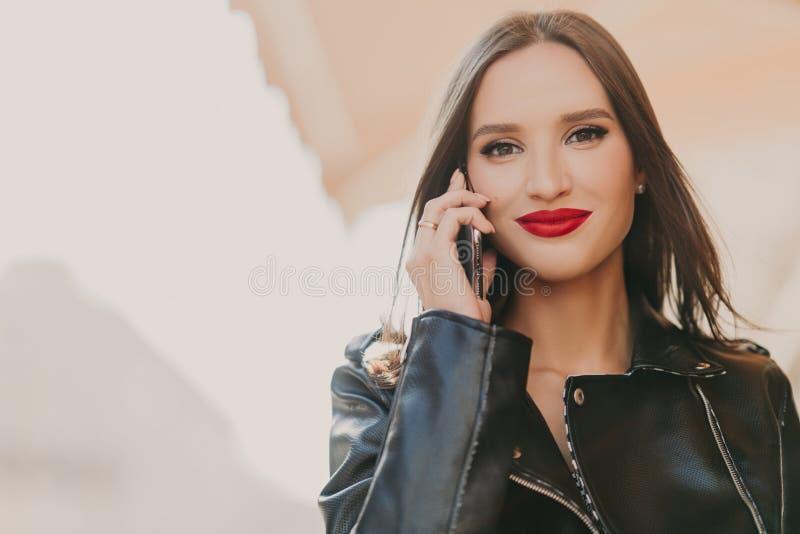 Den attraktiva älskvärda kvinnlign tycker om tariffar, i att ströva omkring, samtal på mobiltelefonen med bästa vän, iklädd trend royaltyfri foto