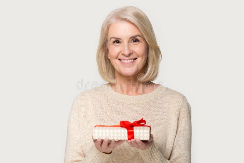 Den attraktiva åldriga asken för kvinnainnehavgåvan känner det lyckliga studioskottet arkivfoto