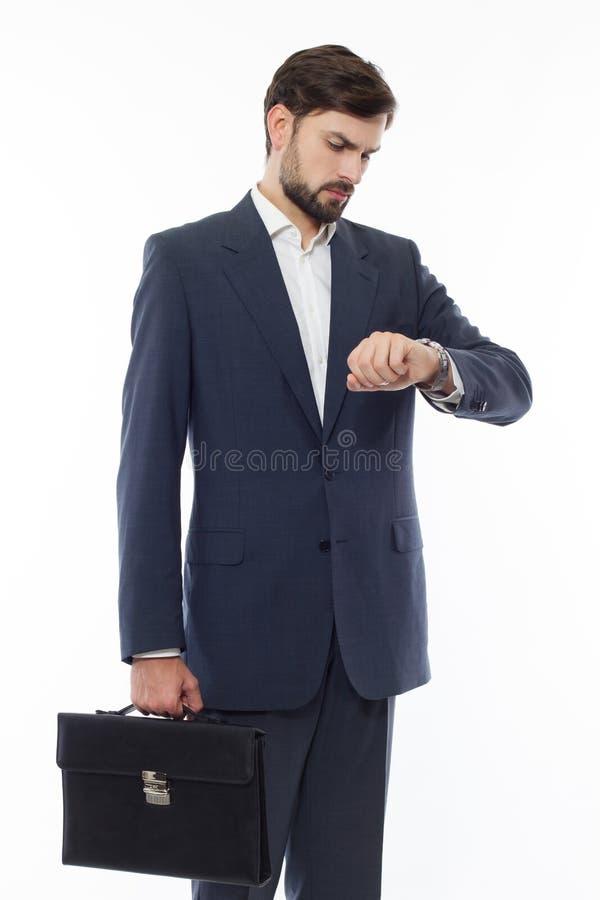 Den attraktiva affärsmannen med resväskan ser klockan royaltyfri bild