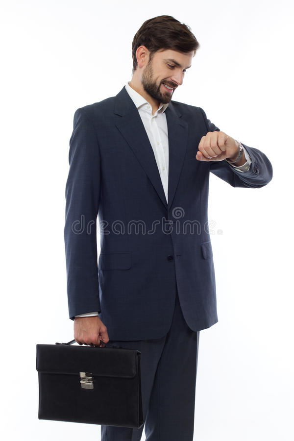Den attraktiva affärsmannen med resväskan ser klockan royaltyfria foton