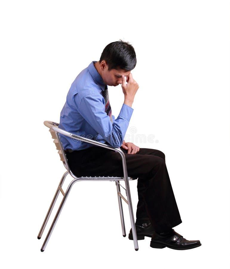 Den attraktiva affärsmannen sitter och tänka över vit royaltyfri bild