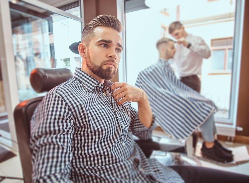 Den attraktiva ansade mannen sitter, medan vänta på en barberare på den upptagna frisersalongen arkivbilder