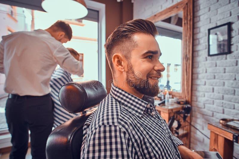 Den attraktiva ansade mannen sitter, medan v?nta p? en barberare p? den upptagna frisersalongen royaltyfri bild