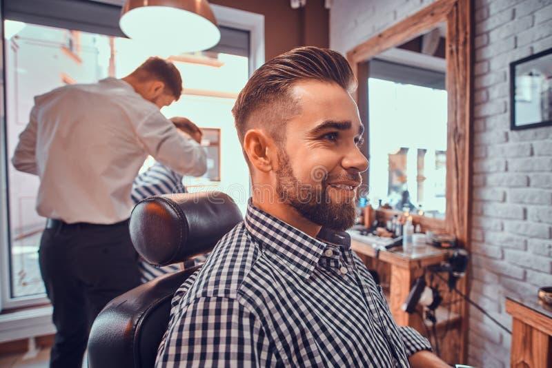 Den attraktiva ansade mannen sitter, medan v?nta p? en barberare p? den upptagna frisersalongen arkivbilder