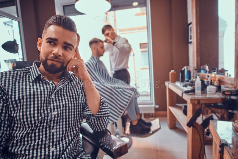 Den attraktiva ansade mannen sitter, medan v?nta p? en barberare p? den upptagna frisersalongen royaltyfria bilder