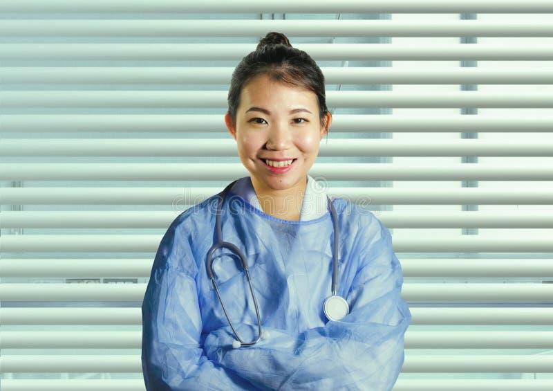 Den attraktiva asiatiska koreanska medicindoktorskvinnan i blått skurar le gladlynt posera företags på sjukhuskontorsfönstret i h royaltyfri fotografi