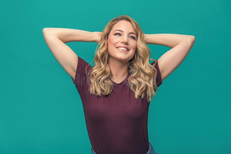 Den attraktiva blondinen jublar med hennes händer bak hennes huvud som kopplar av och ler Härlig ung kvinna på blått arkivbild