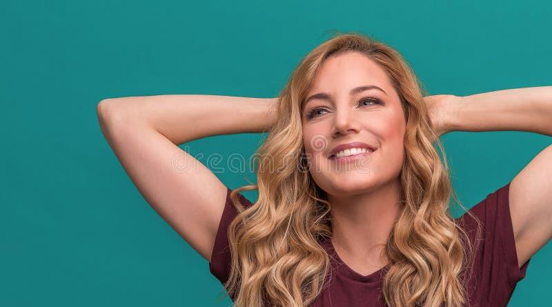 Den attraktiva blondinen jublar med hennes h?nder bak hennes huvud som kopplar av och ler H?rlig ung kvinna p? bl?tt fotografering för bildbyråer