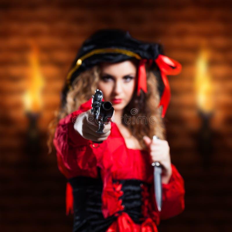 Den attraktiva brunetten piratkopierar flickan med ett vapen arkivbilder