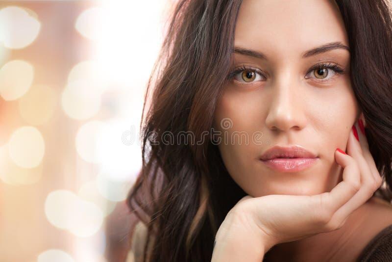 den attraktiva brunettflickan tänder ståenden arkivfoton