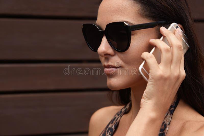 Den attraktiva brunettkvinnan i mörk solglasögon har telefonkonversation på mobiltelefonen utomhus och att se avstånd, ser lugna, royaltyfri foto