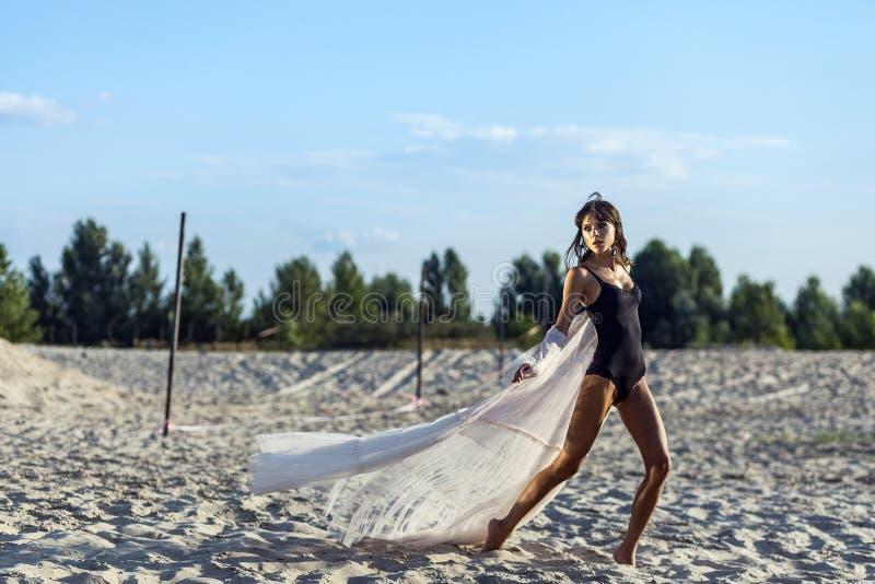 Den attraktiva brunettkvinnan i svart kropp och den genomskinliga stranden täcker upp att posera på den sandiga stranden på solne arkivfoton