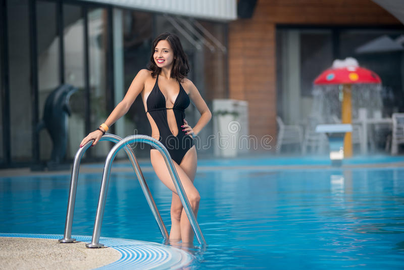 Den attraktiva brunettkvinnan poserar i simbassängen i en svart sexig baddräkt på semesterort med suddig bakgrund royaltyfria bilder