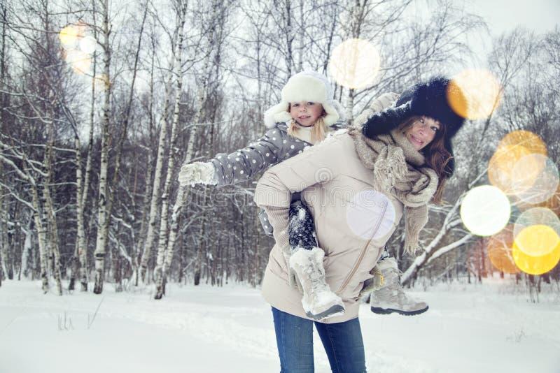 Den attraktiva den familjmodern och dottern som har gyckel i en vinter, parkerar royaltyfria bilder
