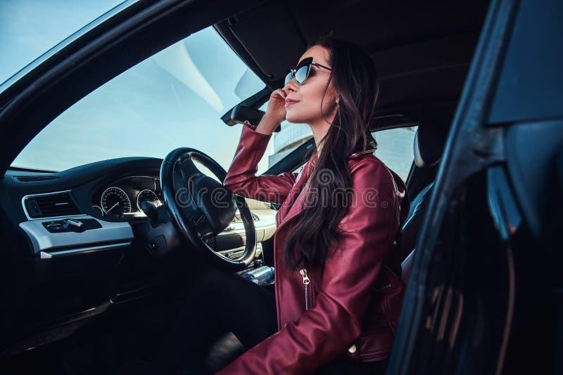 Den attraktiva eftertänksamma kvinnan i rött omslag och solglasögon poserar i hennes bil arkivbild