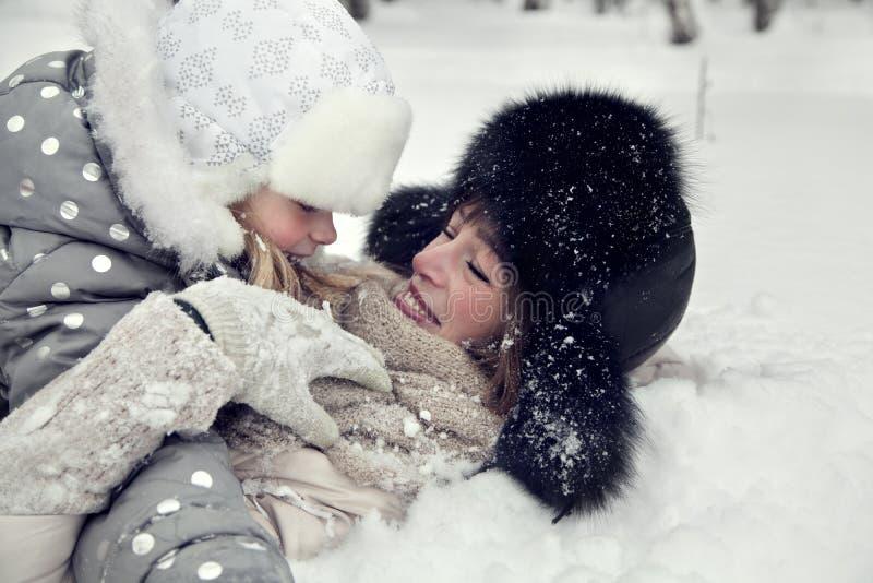 Den attraktiva familjmodern och dottern lägger på ett insnöat en vinter parkerar royaltyfri fotografi