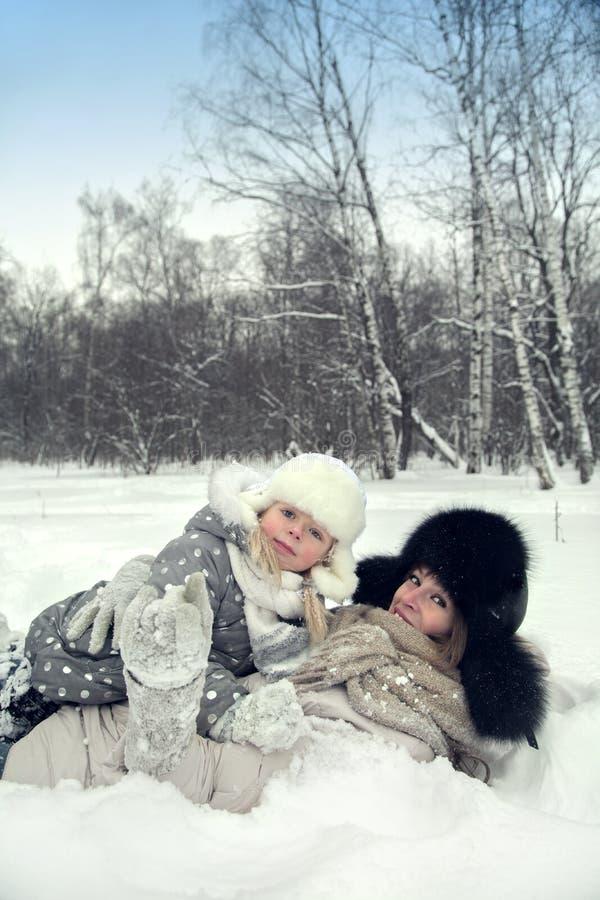 Den attraktiva familjmodern och dottern lägger på ett insnöat en vinter parkerar royaltyfri bild