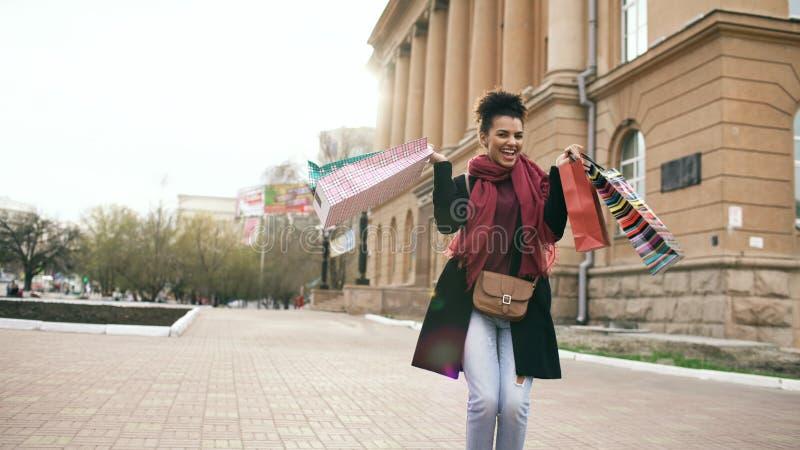 Den attraktiva flickadansen för blandat lopp och har gyckel, medan gå ner gatan med påsar Lycklig ung kvinna som after går royaltyfri foto